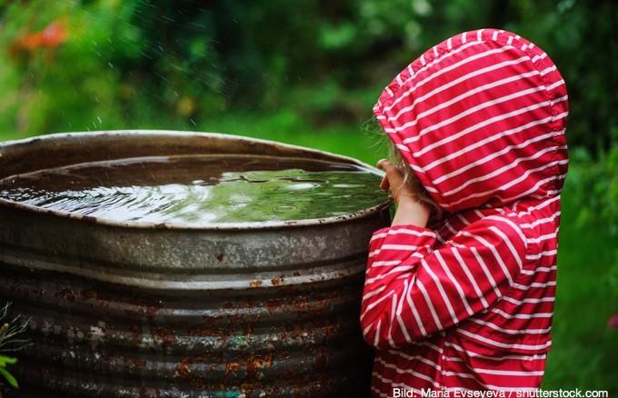 Kind spielt am Regenfass