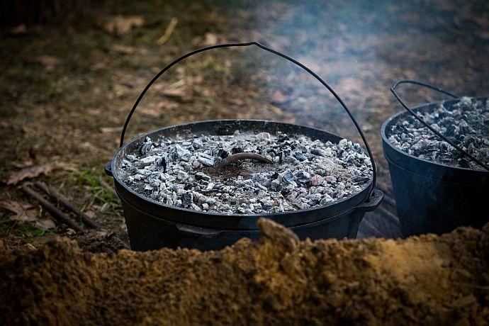 Dutch Oven - glühende Kohlen auf hochgezogenem Deckel