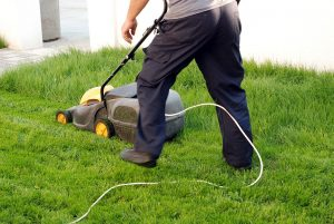 Mann mäht mit einem Elektro-Rasenmäher