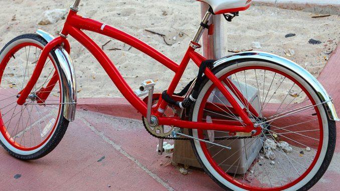 Fahrrad mit Kettenschloss am Pfeiler gesichert