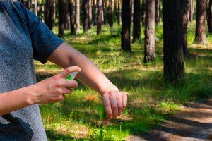Frau sprüht Insektizid auf ihre Haut