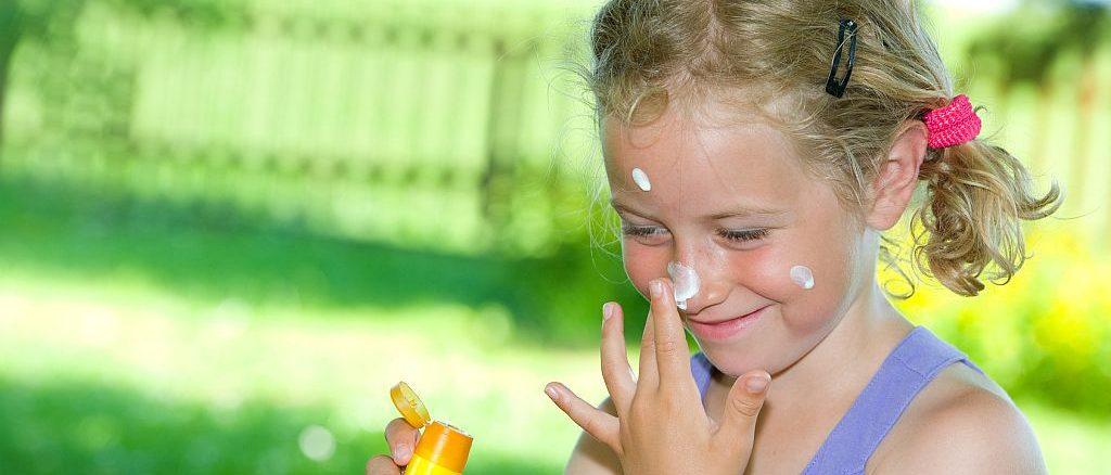 Mädchen im Garten trägt Sonnenschutz auf