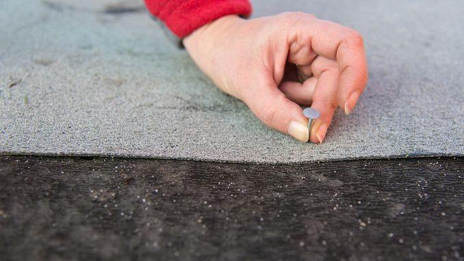 Frau sichert Dachpappe mit Dachpappennagel | Bild: Janni fotolia.com